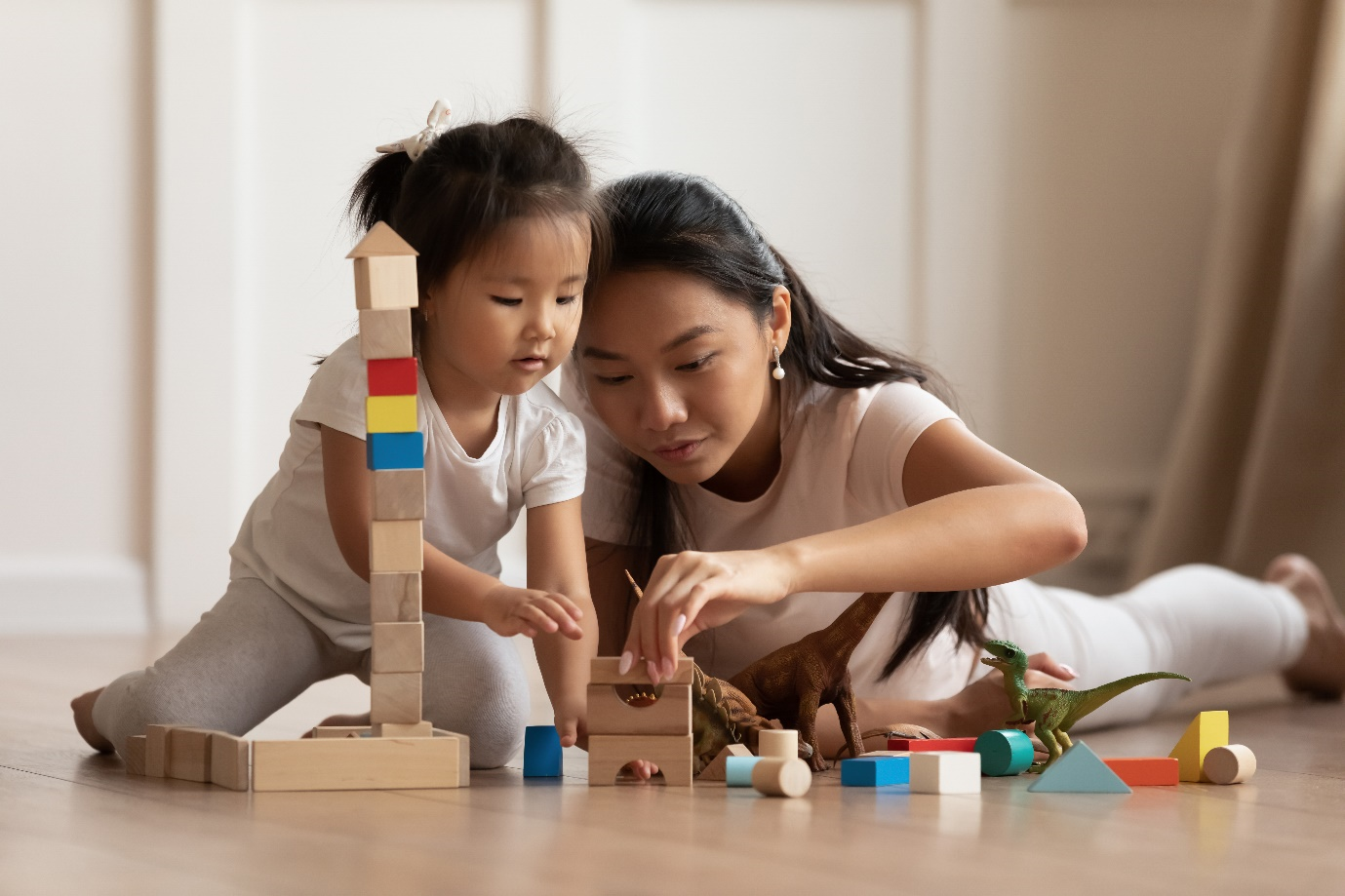 Mum and little girl sitting on floor together stacking blocks