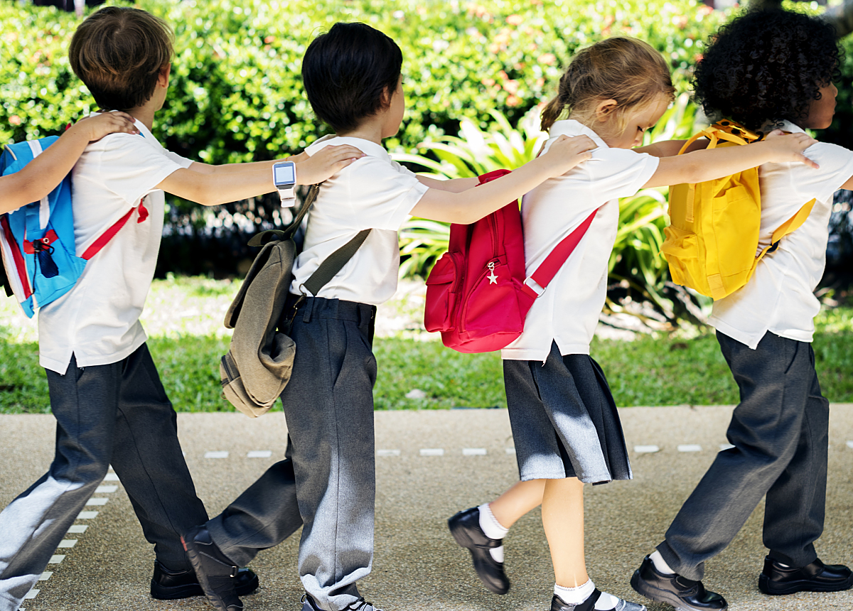 four school children walking to school linked in a chain