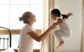 Mum holding daughter as she bounces on bed