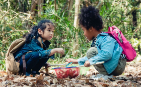 children outside collecting leaves in a net