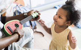 little girl watching her dad play a ukelele