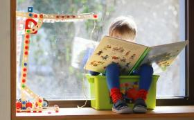 Child sat in a plastic box reading a book