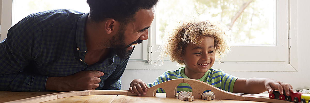 Dad and child playing with train